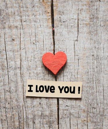 Foto de Te amo texto sobre un fondo de madera con un corazón rojo. - Imagen libre de derechos