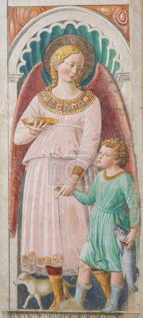 San Gimignano, Italy - July 11, 2017: Fresco in the Church of Sant Agostino in San Gimignano, Tuscany, Italy, depicting Archangel Raphael and Tobias