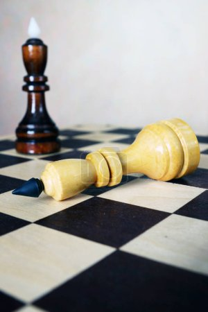 Losing. One chess king lies in front of another one on a chessboard. Conceptual image