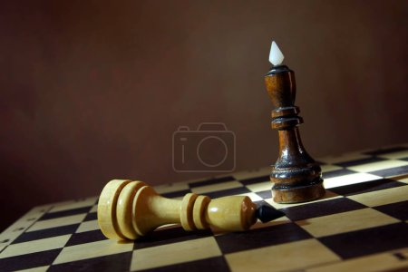 Black chess king won white one. Victory and defeat. Concept with wooden chess pieces