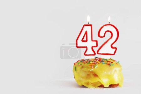 Photo pour Quarante-deux ans. cupcake d'anniversaire avec des bougies blanches brûlantes avec bordure rouge sous la forme du numéro Quarante-deux. Fond gris clair avec espace de copie - image libre de droit