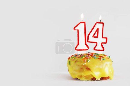 Photo pour Quatorze ans. cupcake d'anniversaire avec des bougies blanches brûlantes avec bordure rouge sous la forme du numéro quatorze. Fond gris clair avec espace de copie - image libre de droit