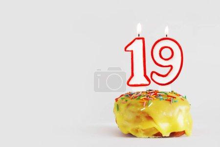 Photo pour Dix-neuf ans. cupcake d'anniversaire avec des bougies blanches brûlantes avec bordure rouge sous la forme du numéro dix-neuf. Fond gris clair avec espace de copie - image libre de droit