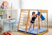 A small child is engaged in boxing on a wooden home sports complex. Girl in boxing gloves hits the pear. Children's physical development.