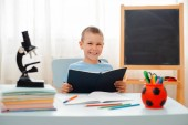 school boy sitting at home classroom lying desk filled with books training material schoolchild sleeping lazy bored