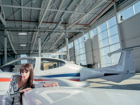 Photo for Young brunette woman in silver dress posing by small aircraft - Royalty Free Image