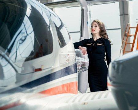 Photo pour Séduisante fille en robe noire posant près de l'avion - image libre de droit