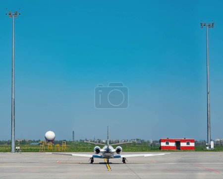 Photo for Scenic view of sun lighted airport with plane and blue sky - Royalty Free Image