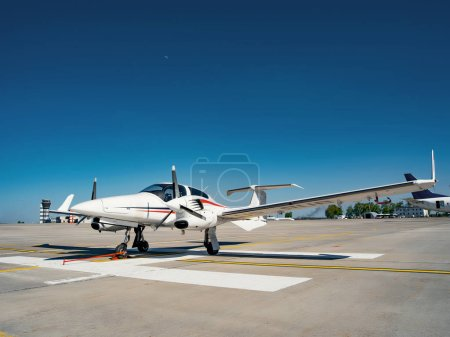 Photo for Airport scene with small airplane in bright sunlight - Royalty Free Image