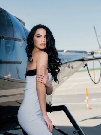 Photo pour Belle jeune femme modèle posant près de l'hélicoptère - image libre de droit