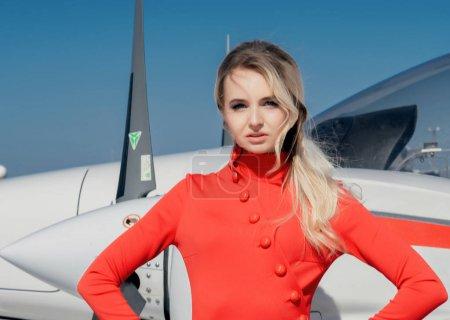 Photo pour Modèle portant une robe rouge posant par avion en plein soleil - image libre de droit