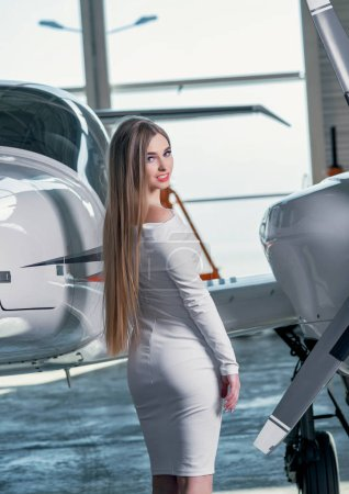 Photo for Young woman in white dress posing near aircraft - Royalty Free Image