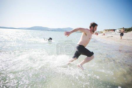Man wearing swimsuits splashing around having fun with his dog