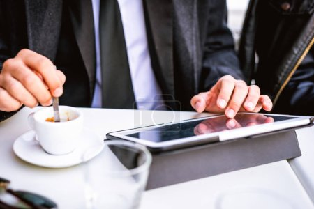 Close up on the hands of young businessman stirring with a tablespoon a cup of coffee and using tablet, tapping screen