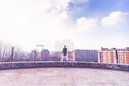 Photo pour Vue de l'arrière d'un jeune homme se tenant loin de tout - paix et tranquillité, solitude, concept d'indépendance - image libre de droit