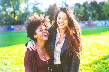 Photo pour Deux jeunes femmes étreignant marche s'amuser - image libre de droit