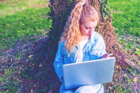 Photo pour Jeune femme blonde en utilisant ordinateur portable adossée à un tronc dans un parc de la ville - image libre de droit
