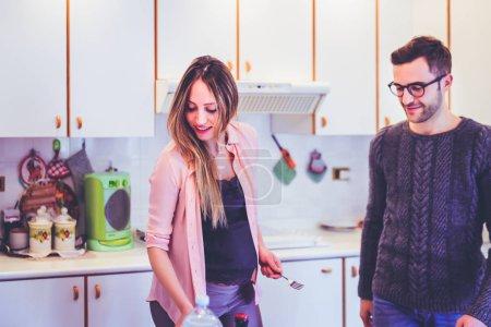 Photo pour Jeune couple de femmes enceintes à la maison s'amuser à préparer la nourriture - bonheur, vie commune, concept de temps de qualité - image libre de droit