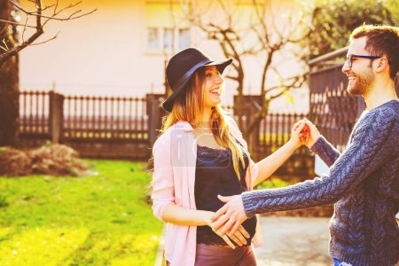 Photo pour Jeune couple enceinte à l'extérieur s'amuser contre-jour bonheur, vie de famille, concept de temps de qualité - image libre de droit