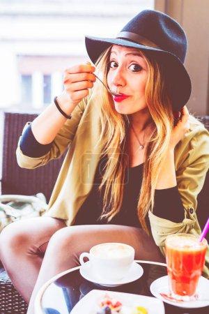 Photo pour Jeune femme assise au bar avec cappuccino - nourriture et boisson, petit déjeuner, concept de détente - image libre de droit
