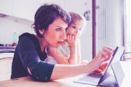Photo pour Mère et fille à l'intérieur en utilisant des comprimés - concept d'apprentissage, de divertissement, d'enseignement - image libre de droit