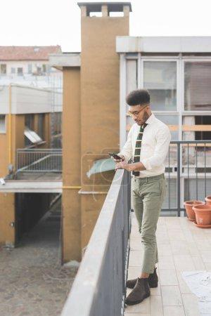 Photo pour Jeune homme noir en plein air utilisant le téléphone intelligent - affaires, télétravail, concept technologique - image libre de droit