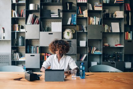 Photo for Young black student working with tablet on a project in coworking office - imaginative, education, concentration concept - Royalty Free Image
