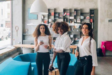 Photo pour Trois jeunes femmes d'affaires multiculturelles se tenant debout avec un smartphone dans un loft moderne - concept inventif, indépendant, dévoué - image libre de droit