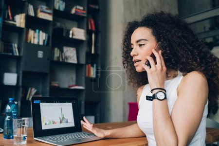 Photo for Young brunette woman having business call and working in modern office with laptop - emancipation, concentration, dedication concept - Royalty Free Image