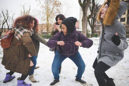 Photo pour Groupe de copines twerking dans le parc avec couverture de neige mouvement, relation, concept de plaisir - image libre de droit