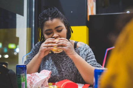 Photo for Young african woman eating in fast food - appetite, break, relax concept - Royalty Free Image