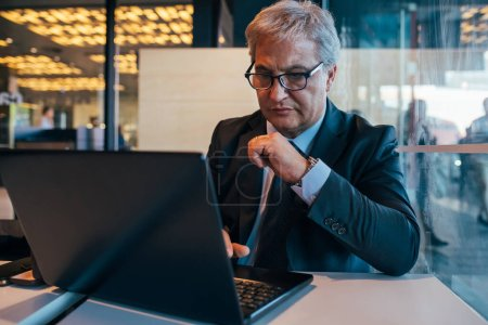 Photo for Businessman indoors using computer - busy mature professional worker in office planning using laptop - Royalty Free Image