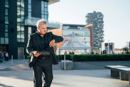 Photo for Middle-age contemporary businessman outdoor in the city, using tablet hand hold checking the time - business, work, communication concept - Royalty Free Image