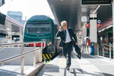 Photo for Professional senior businessman running railway station - Businessman late for work running on train platform - Royalty Free Image