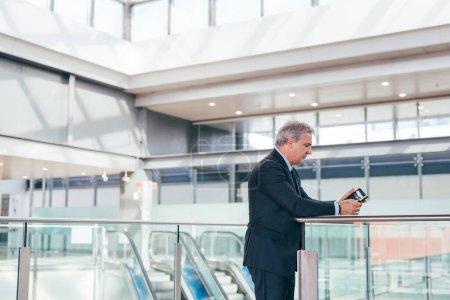 Photo pour Homme d'affaires adulte moyen utilisant un smartphone à l'intérieur - Élégant terminal de l'aéroport homme de travail téléphone mobile - image libre de droit