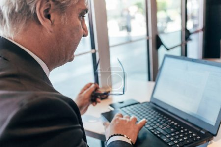 Photo for Middle-age contemporary businessman indoor in the city sitting bar, using laptop computer - business, work, communication concept - Royalty Free Image