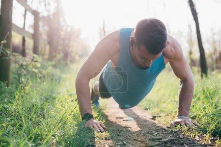 Photo pour Entraînement en plein air contre-jour jeune homme dans la ville - exercice, mode de vie sain, concept sportif - image libre de droit