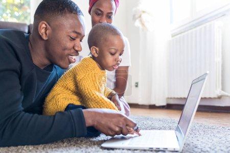 Photo pour Famille heureuse à l'intérieur avec tout-petit en utilisant un ordinateur portable divertissement, apprentissage, concept de technologie - image libre de droit