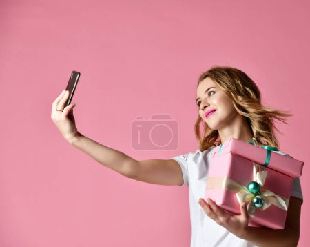 Young beautiful woman hold christmas present gifts...