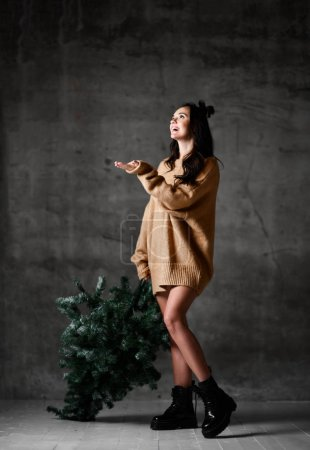 Sexy hipster woman hold Christmas fir tree in knit...