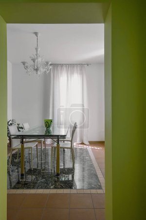 Photo for Interiors shots of a contemporary dining room with glass dining table and classic glass chandelier - Royalty Free Image
