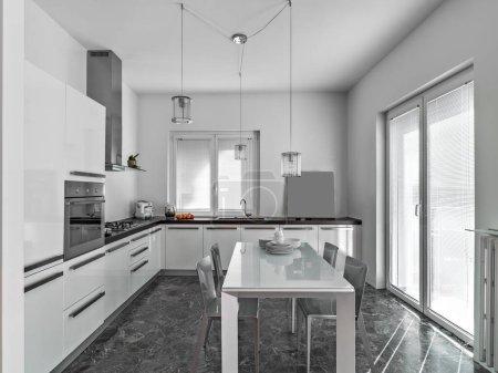 Photo pour Intérieurs d'une cuisine moderne avec des armoires en lichen wahite, au centre de la pièce, il y a la table à manger le sol est fait en matble - image libre de droit
