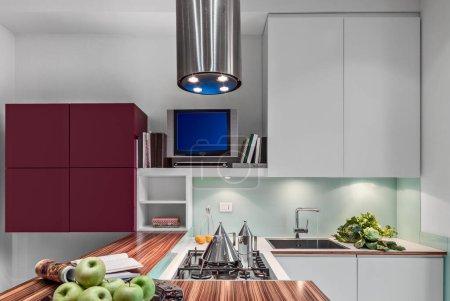 Photo pour Intérieurs d'une cuisine moderne au premier plan la plaque de cuisson au gaz sur le fond les armoires murales et l'évier intégré sur le plan de travail - image libre de droit
