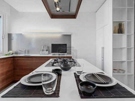 Photo pour Intérieurs d'une cuisine moderne au premier plan la plaque de cuisson au gaz avec table à manger avec plaques sur le fond les armoires de cuisine en bois - image libre de droit