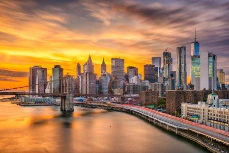 Photo pour Gratte-ciel de Manhattan inférieure de New York, New York, é.-u. sur l'East River, avec le pont de Brooklyn après le coucher du soleil. - image libre de droit