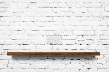 Photo pour Étagère en bois sur fond de mur de briques blanches - image libre de droit