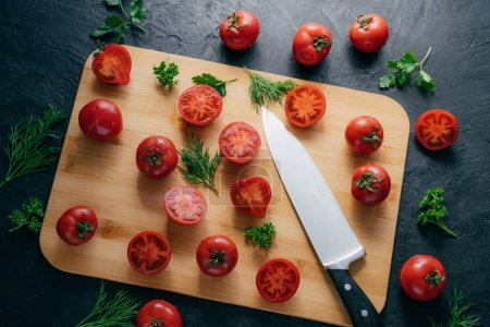 Tasty ripe tomatoes sliced on chopping board with greenery, sharp knife near, isolated over dark background. Kitchenware. Top view.