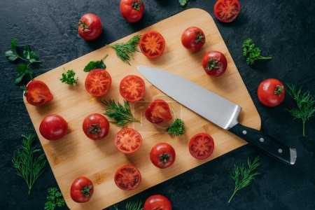 Top view of fresh small red tomatoes sliced on wooden kitchen board with knife. Green parsley and dill near. Vegetables and vitamins