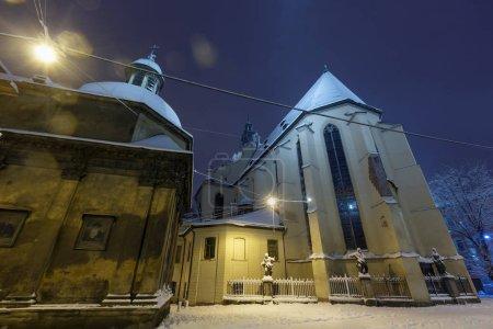 Kathedrale basilika der Himmelfahrt (römisch-katholische erzdiözese) in lviv stadt, ukraine. und Boimskapelle. schöne verschneite Abenddämmerung winterliche Stadtlandschaft. Lampenfackeln verfügbar.