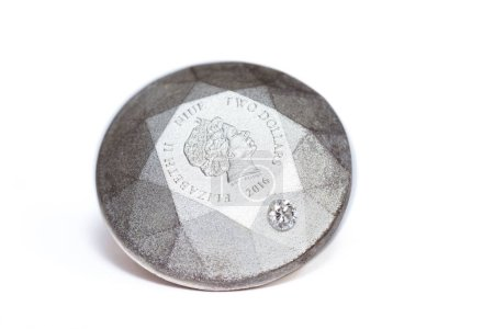 Diamond shape silver coin with a  diamond embedded on to the side of the coin